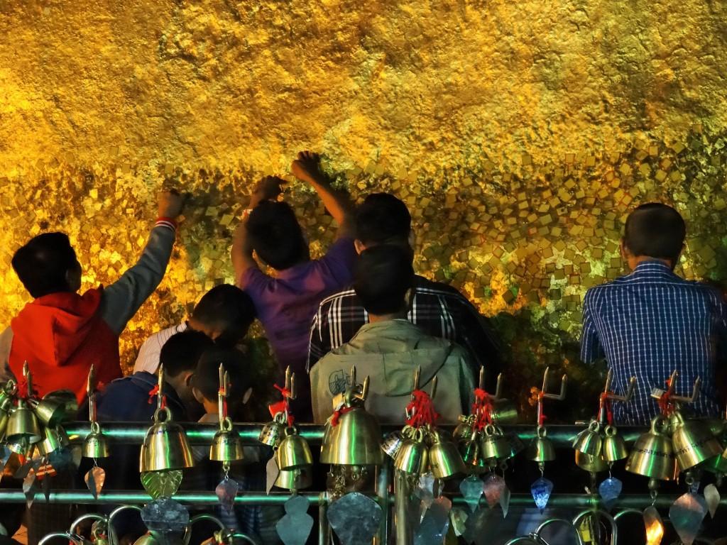 Die Pilger bringen kleine Blattgoldplättchen mit, die sie an den überaus heiligen Felsen kleben